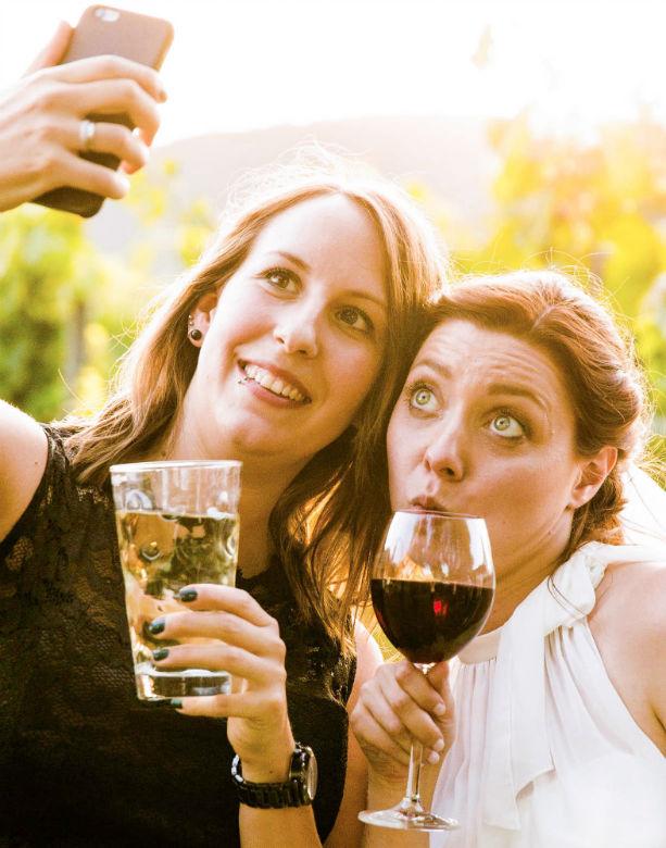 Braut mit Weinglas und Freundin beim Selfie