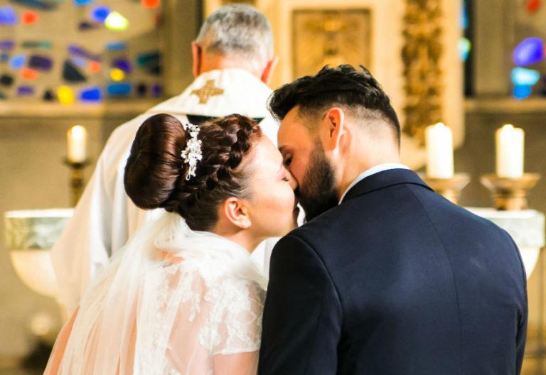Heimlicher Brautpaarkuss hinter dem Pfarrer in der Kirche