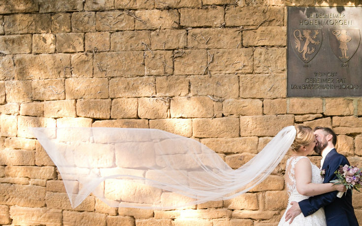 Brautpaarkuss mit wehendem Schleier vor schöner Sandsteinmauer in den Weinbergen
