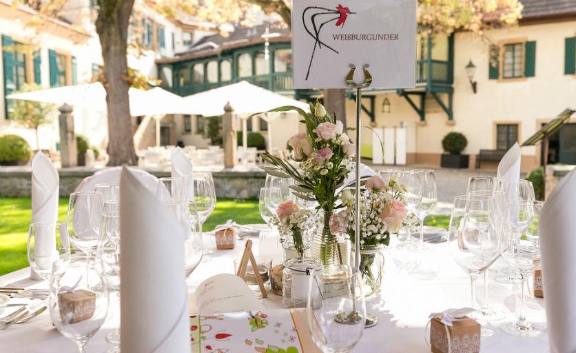 Wunderschön eingedeckter Hochzeitstisch mit Weinnamen und in herrlicher Umgebung